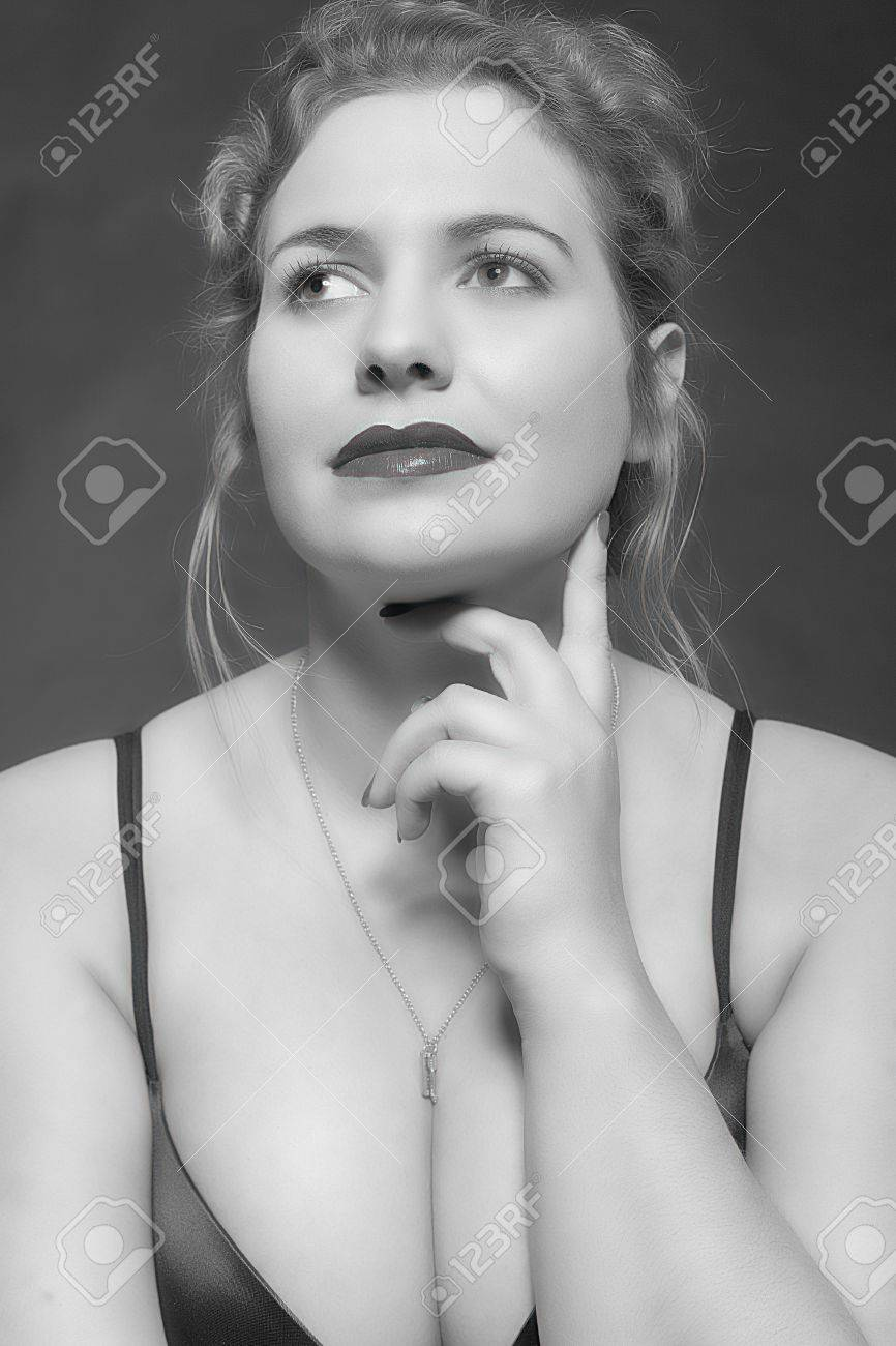 Black white portrait of a friendly looking model in oversized with big breasts in a