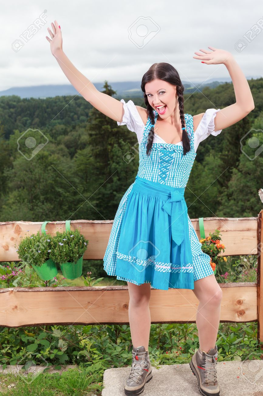 421f2649a4f0 Dancing and waving Knitting Bavarian girl in blue dirndl with much joy in  the face Stock