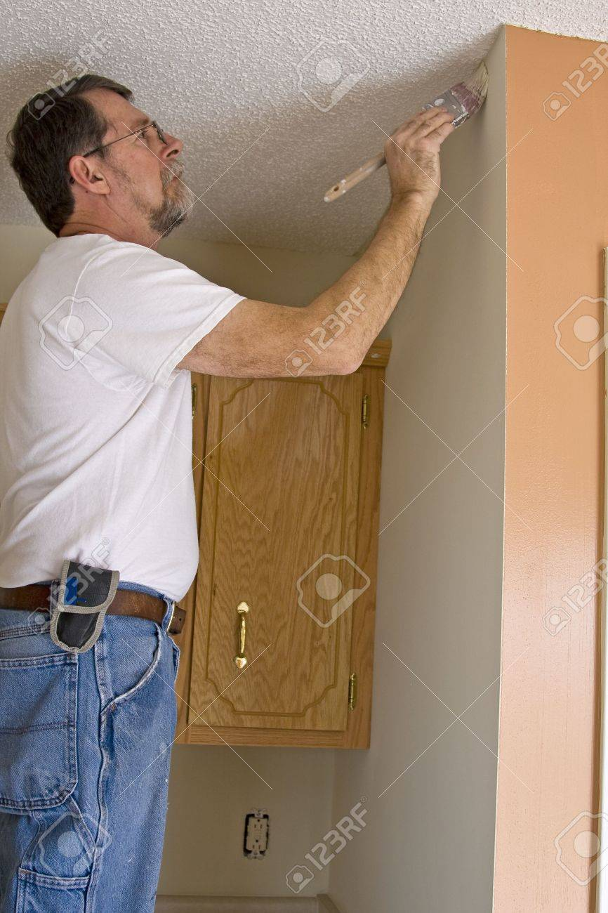 Contract painter updating colors of walls and painting ceilings bright white to speed up selling of home Stock Photo - 2505945