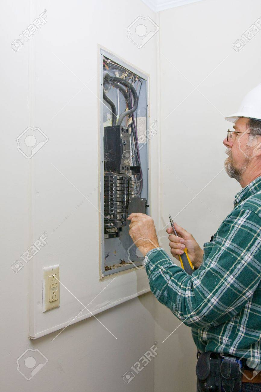 Inspector hired by future home owner, checking circuit breakers for loose connections,defective breakers or any signs of over heating of wiring, Stock Photo - 2801348