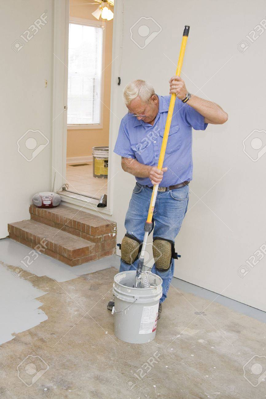 contract painter painting garage floor to speed up selling of home stock photo