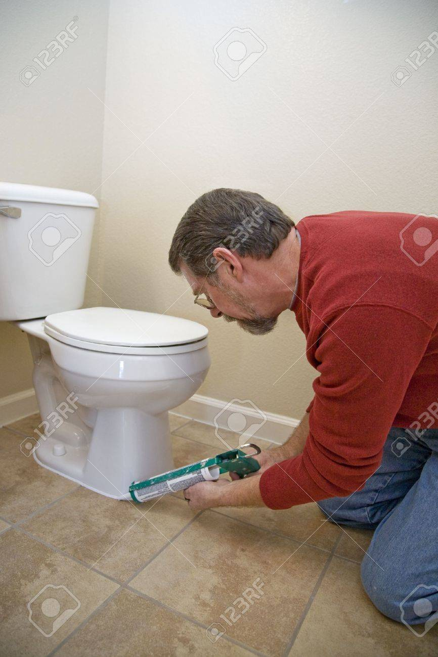 Contractor Caulking Around Toilet To Keep Moisture From Seeping - Bathroom caulking contractors