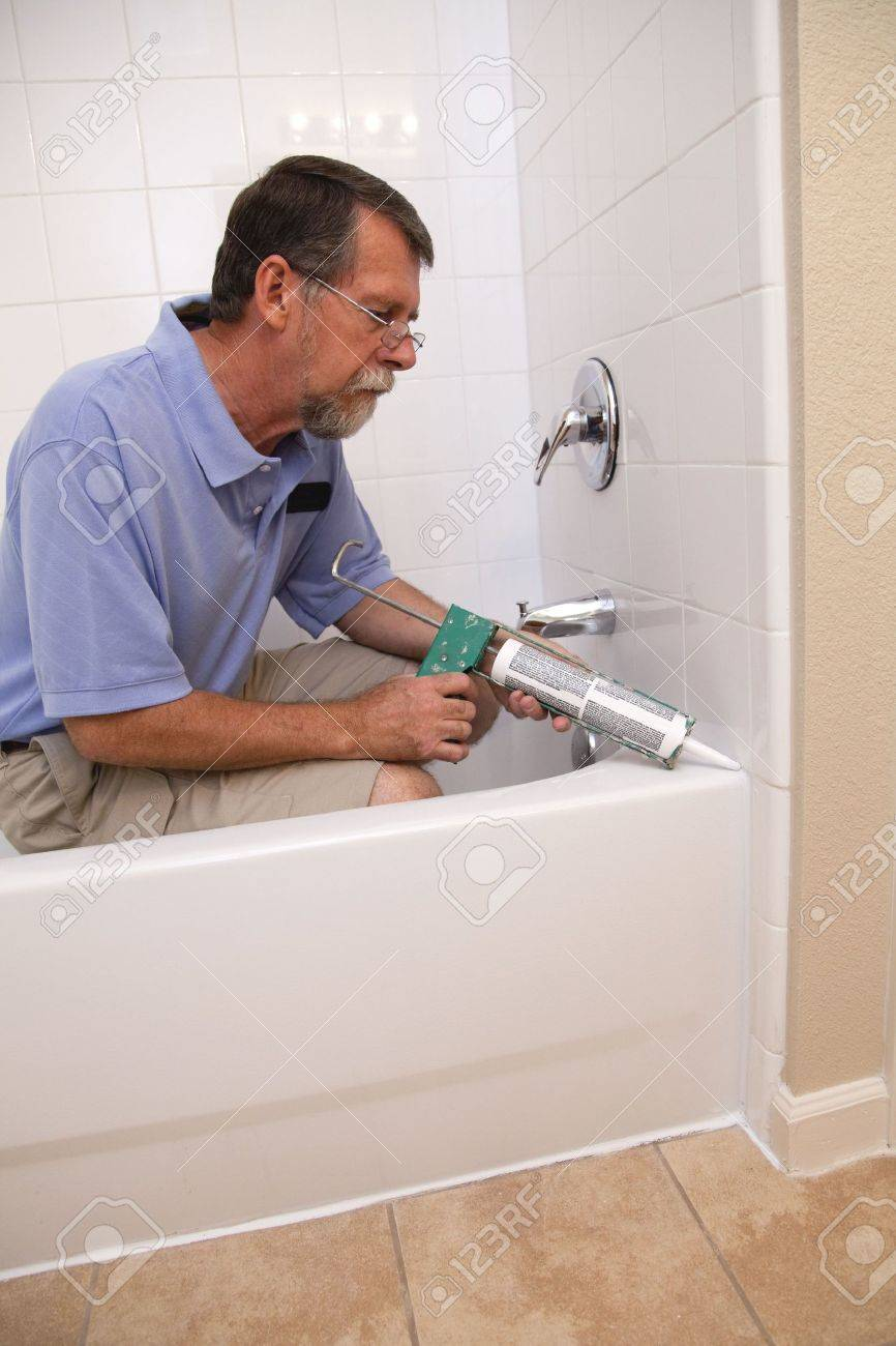 Contractor Caulking Around Tub Sealing To Prevent Possible Water - Bathroom caulking contractors