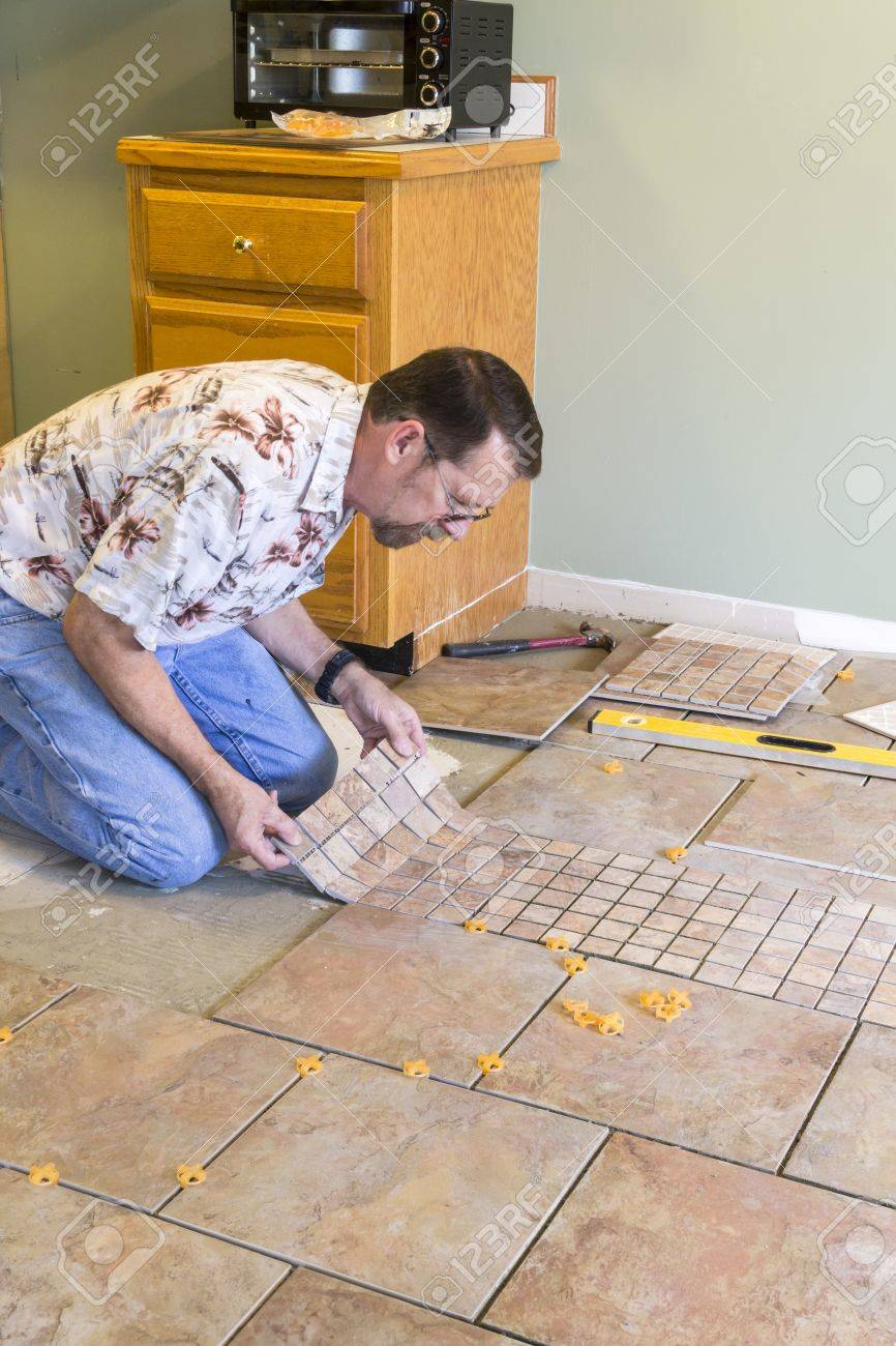 Man installing ceramic tile in customers kitchen getting ready man installing ceramic tile in customers kitchen getting ready to sell home stock photo dailygadgetfo Image collections