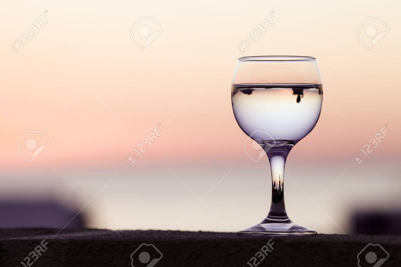 Glass of white vine with reflections of houses and view to beautiful sunset. Selective focus. Toned. - 48661090
