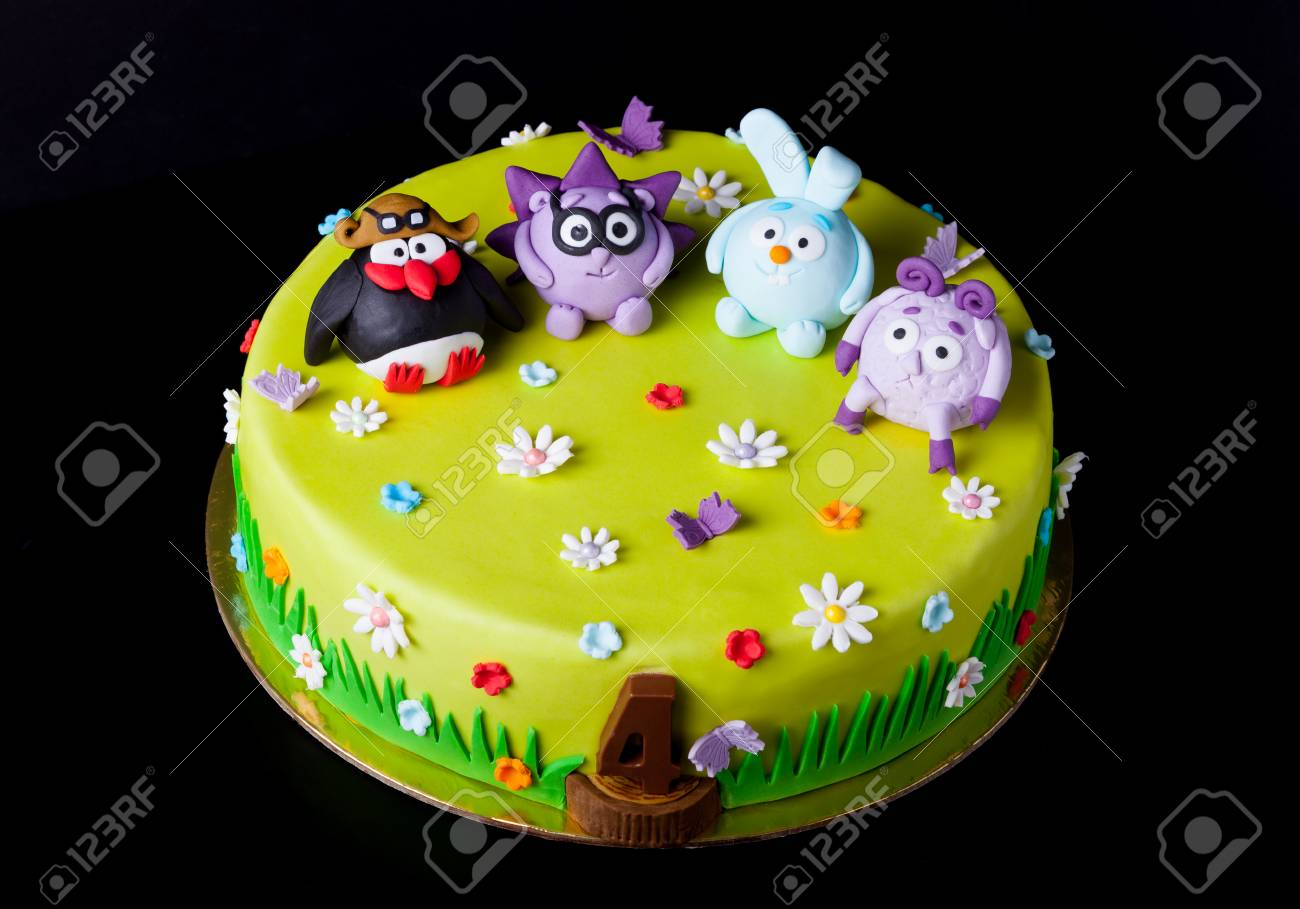 Homemade cake with mastic for children's birthday on a black background. Animation theme - smeshariki. - 75103342