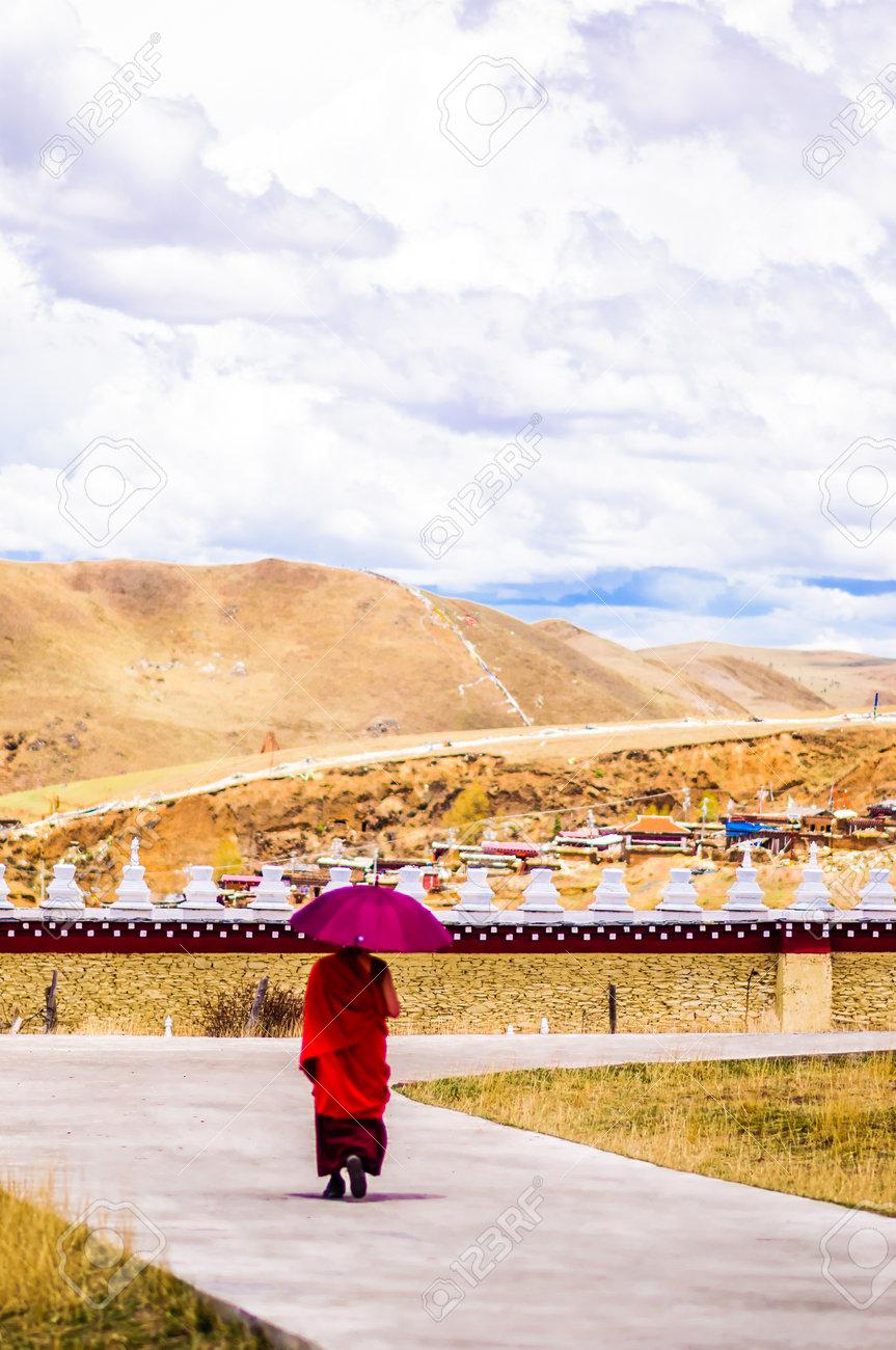 Tagong, China on 12th May 2015 - View on Tibetan monk walking with umrella - 142308261