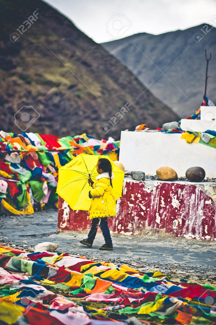 Tagong, China on 12th May 2015 - View on girl with yellow umbrella going arround tibetan stupa - 142308256
