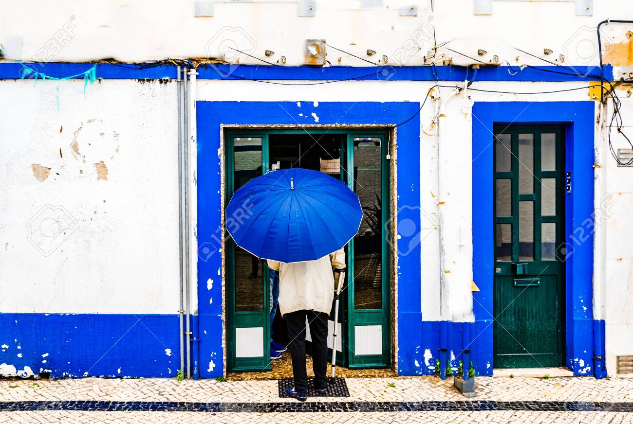 View on Old man with umbrella in front of blue colored building in the city of Ericeira, Portugal - 143742050