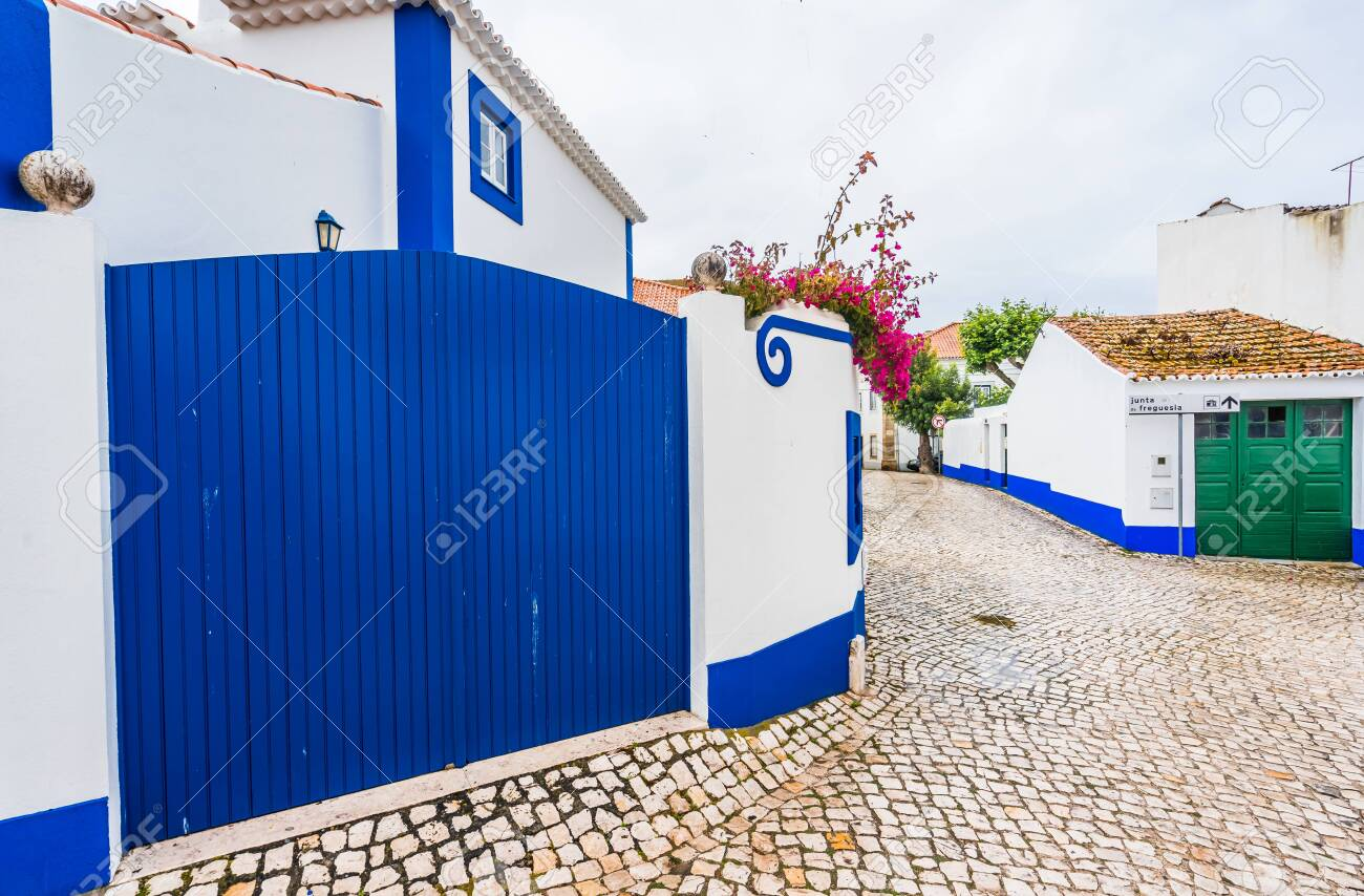View in the streets of Ericeira, traditional white houses with blue stripes, Portugal - 144070054