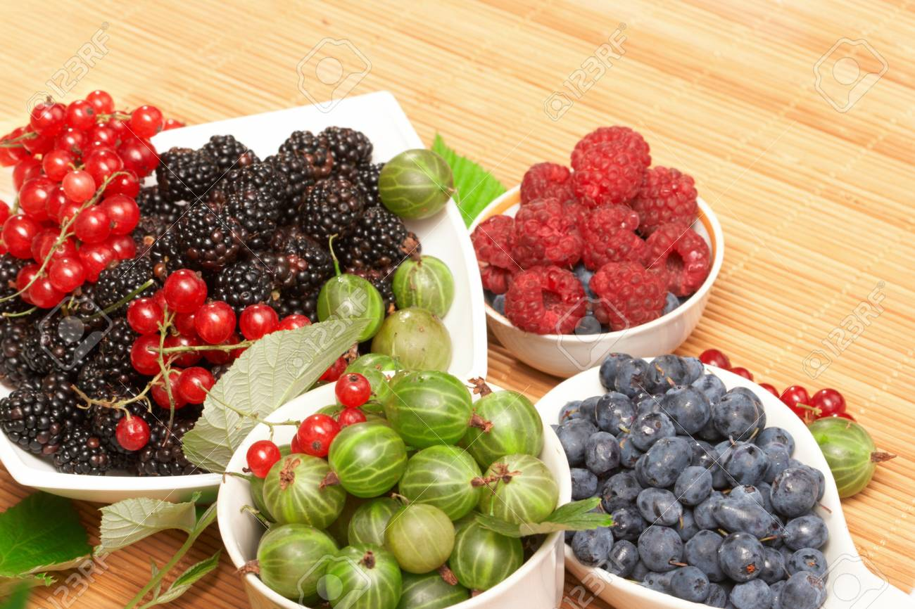 Berries in plates, on a table, among green leaves Stock Photo - 7900854