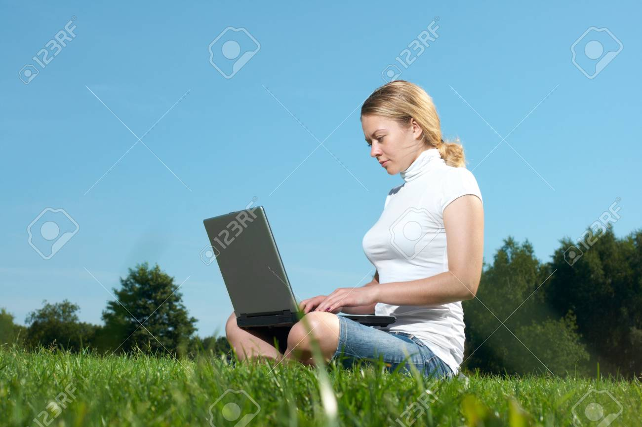The girl with laptop on a green lawn Stock Photo - 8034577