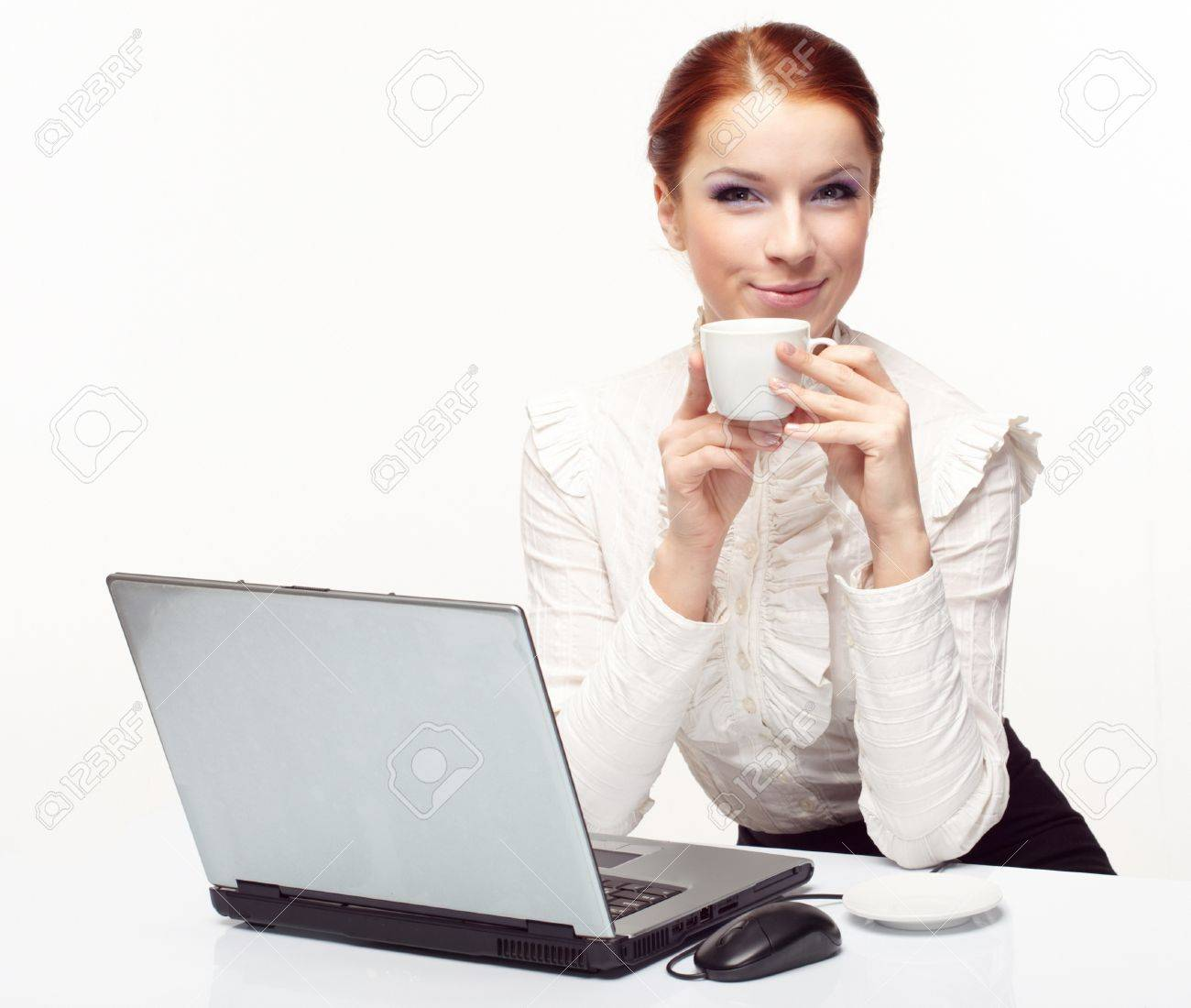 Business woman working on her laptop and drinking coffee. Stock Photo - 8597398