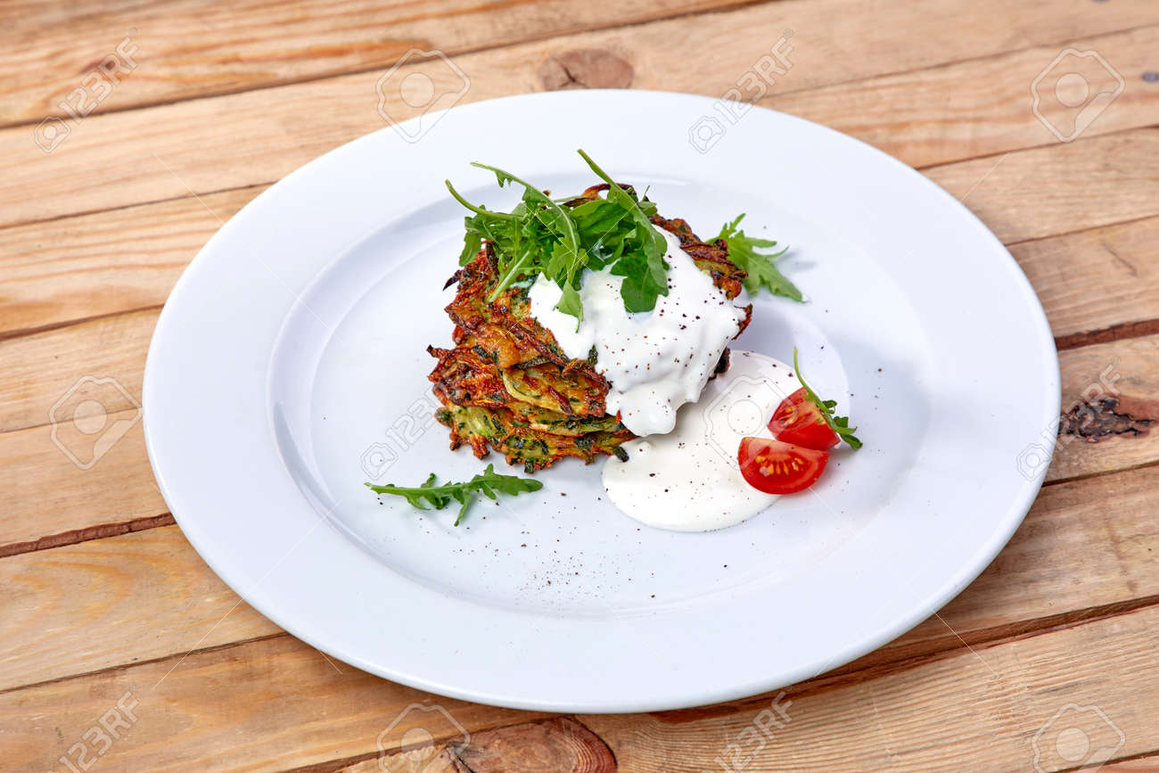Zucchini pancakes with sour cream and herbs - 143006392