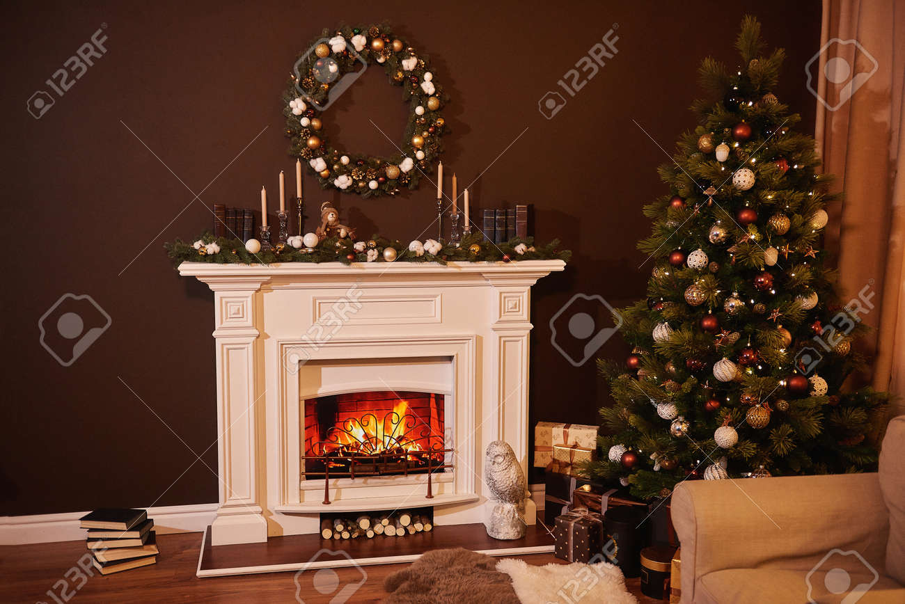 Christmas tree with beautiful balls in a cozy brown living room with a fireplase. Christmas room interior design, Xmas tree decorated by lights, candles and garland lighting indoors fireplace - 157661708