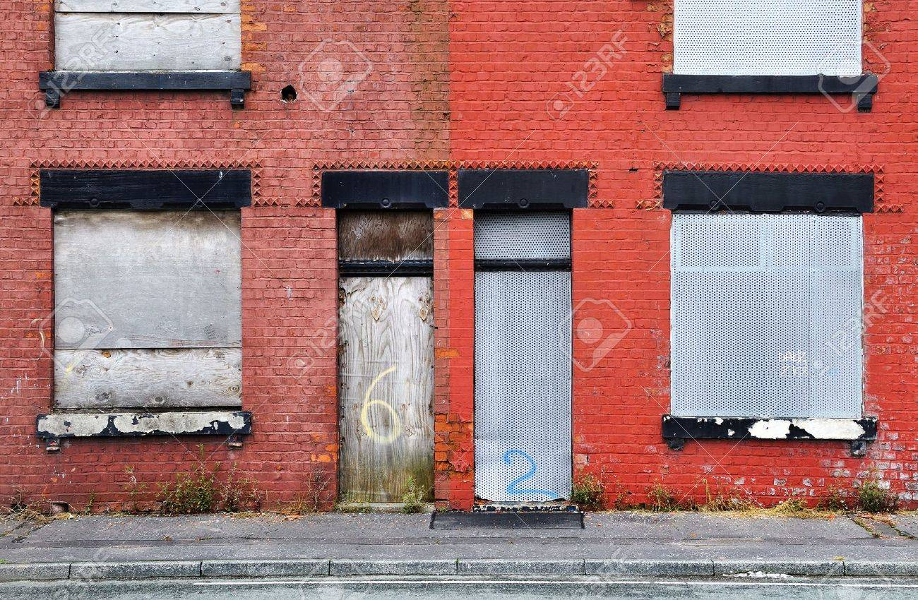 Derelict terraced housing in Salford, UK, boarded up and awaiting demolition - 13354073