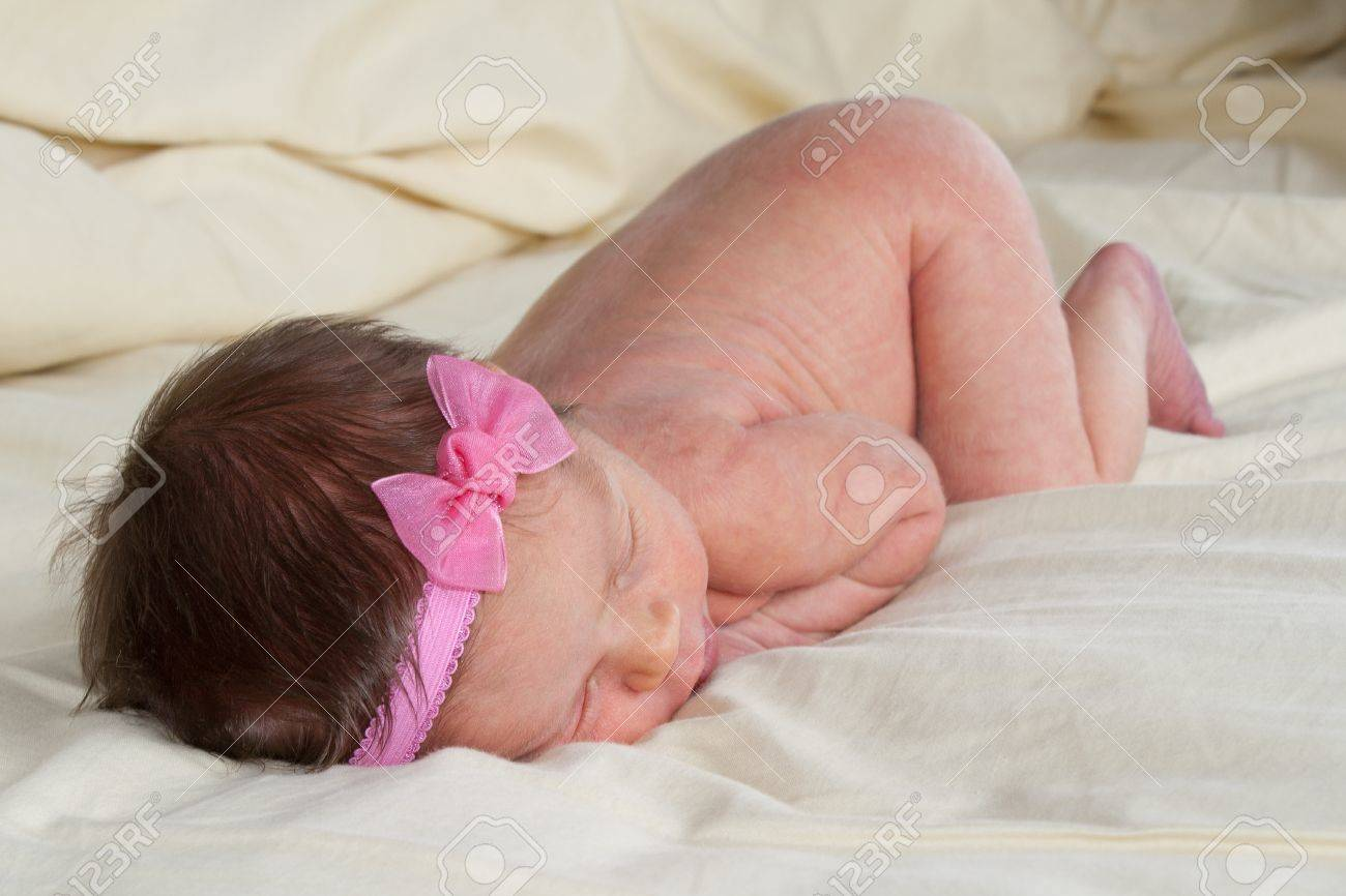 An infant with a pink bow laying on her stomach Stock Photo - 8530632