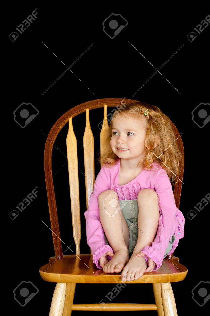 Black child sitting in chair - A Cute Girl Sitting On A Wooden Chair With A Black Background Stock Photo