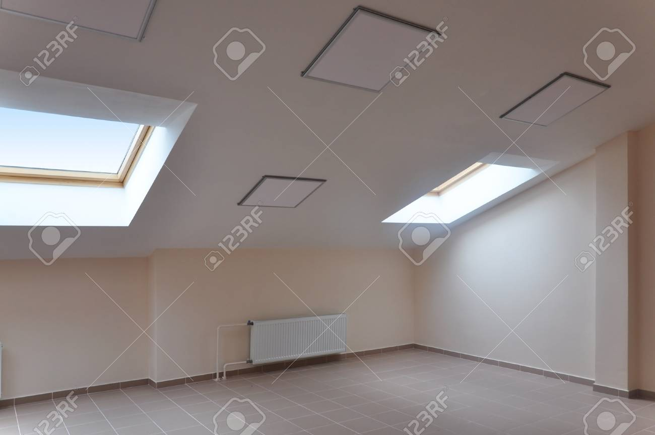 Modern interior of attic room with a sloping ceiling and skylight