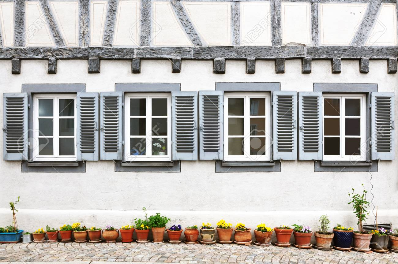 Four Windows With Shutters On The White Facade Of Half Timbered
