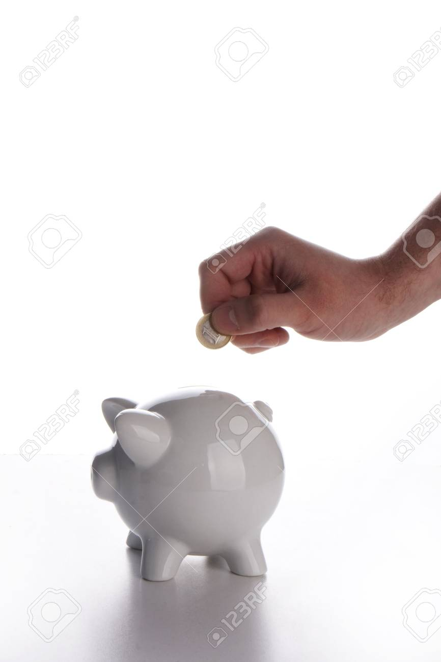 Hand placing a coin into a piggy bank isolated on white Stock Photo - 4792453