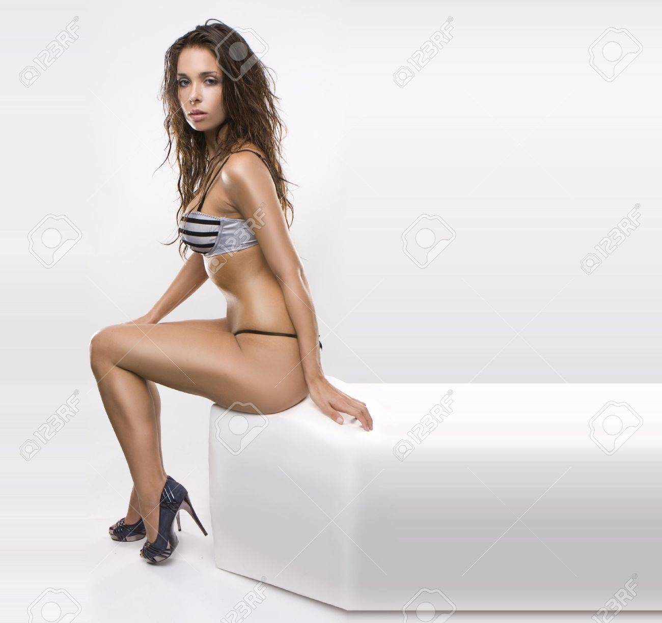 sexy glamour model wearing lingerie and heels sitting on white isolated box, Stock Photo - 5303018
