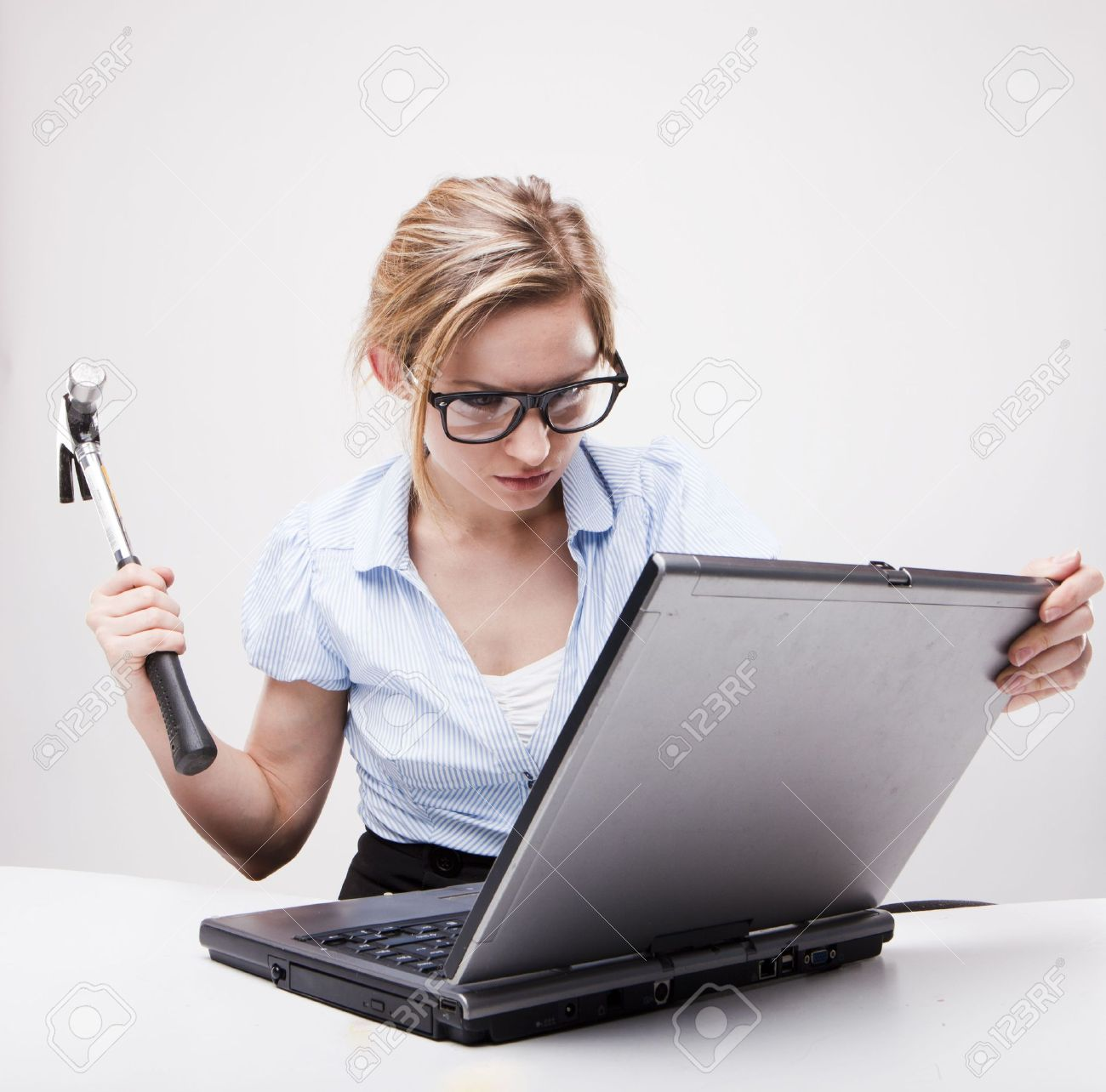 Attractive blond hair woman wearing business suit sitting in front of a computer with angry facial expression holding a hammer and wearing glasses Stock Photo - 7347635