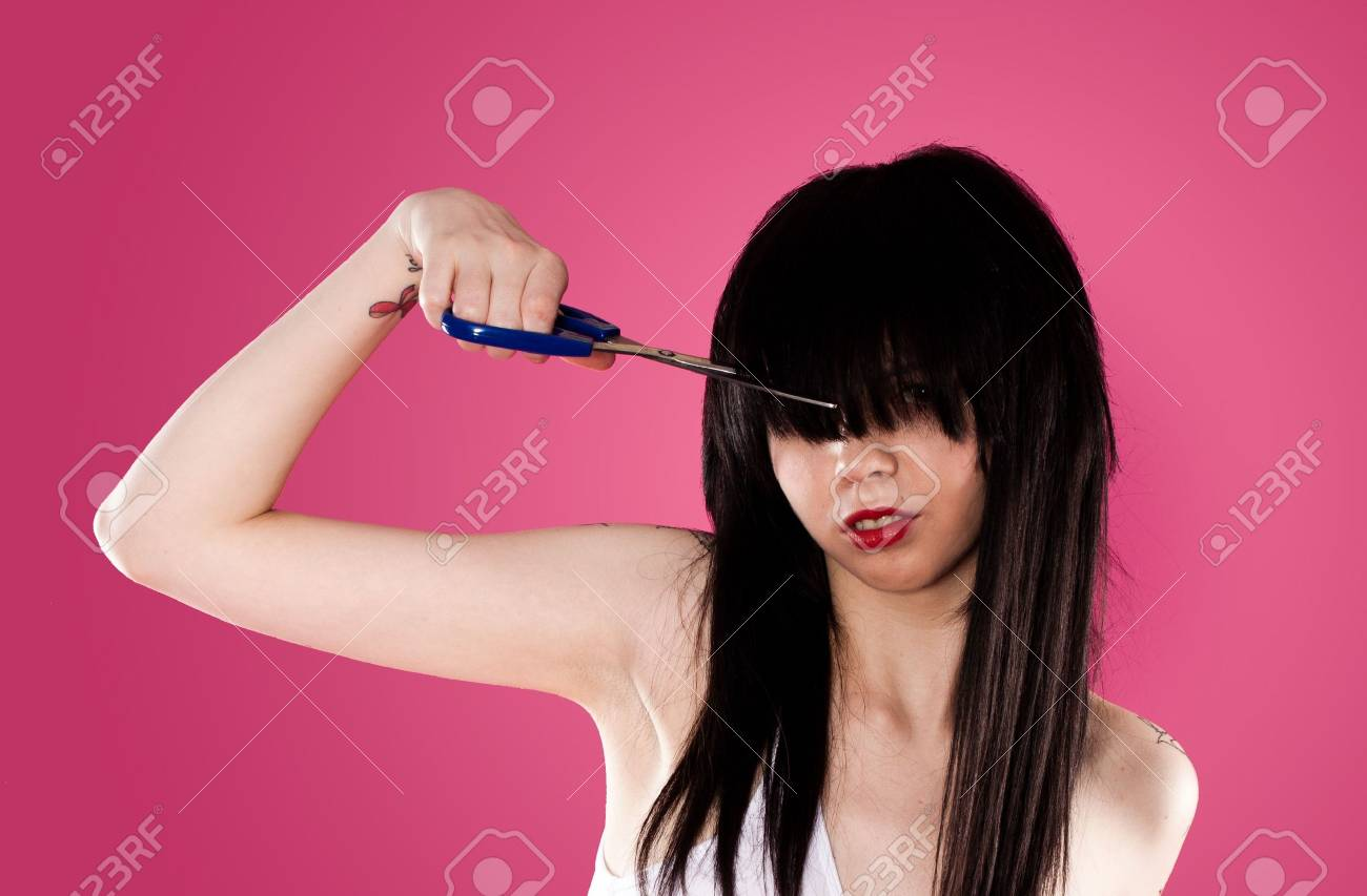 young woman cutting her fringe over pink background Stock Photo - 7587932