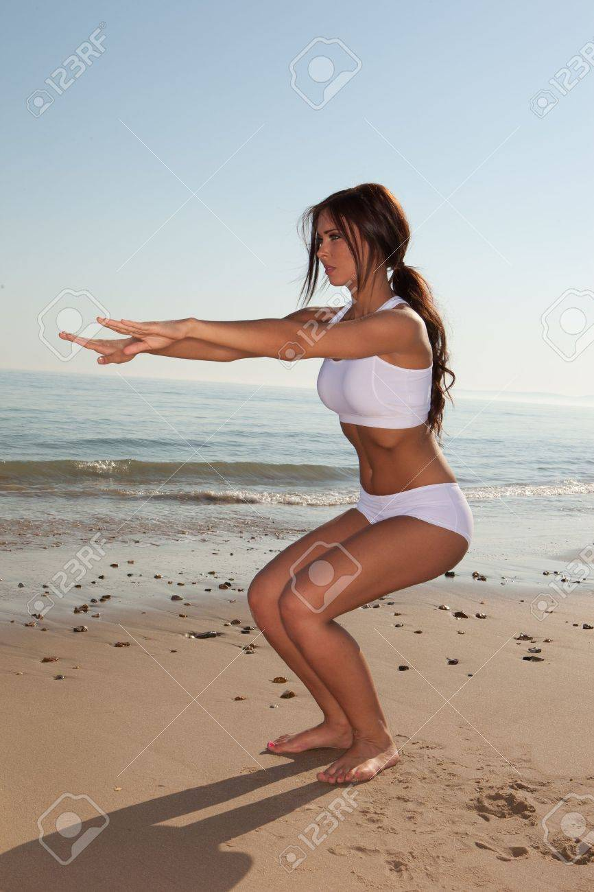 fitness brunette woman exercise on the beach - 9468867