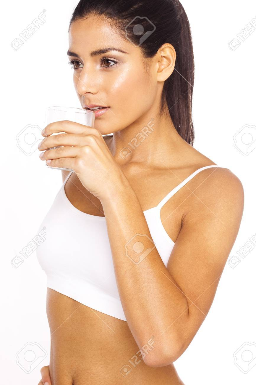 Athlete Drinking Water, an attractive young lady drinks a refreshing glass of water. - 12586078