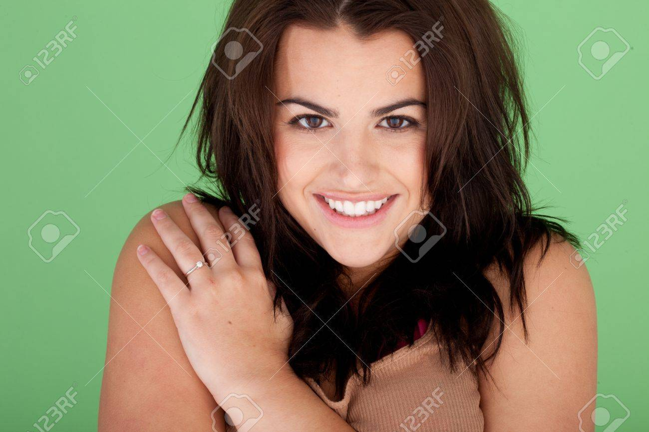 Cheerful natural looking young woman smiling, front view with hand on shoulder pose, green background, Stock Photo - 12586889
