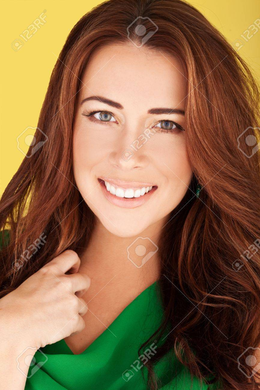 Smiling redhead women wearing emerald green dress, in beauty and glamour portrait on yellow. - 12589597