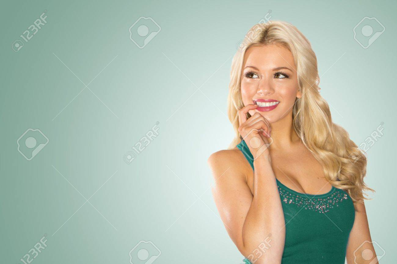 Smiling Pensive Blonde lady with her finger to her mouth looking back in to the frame. - 12586132