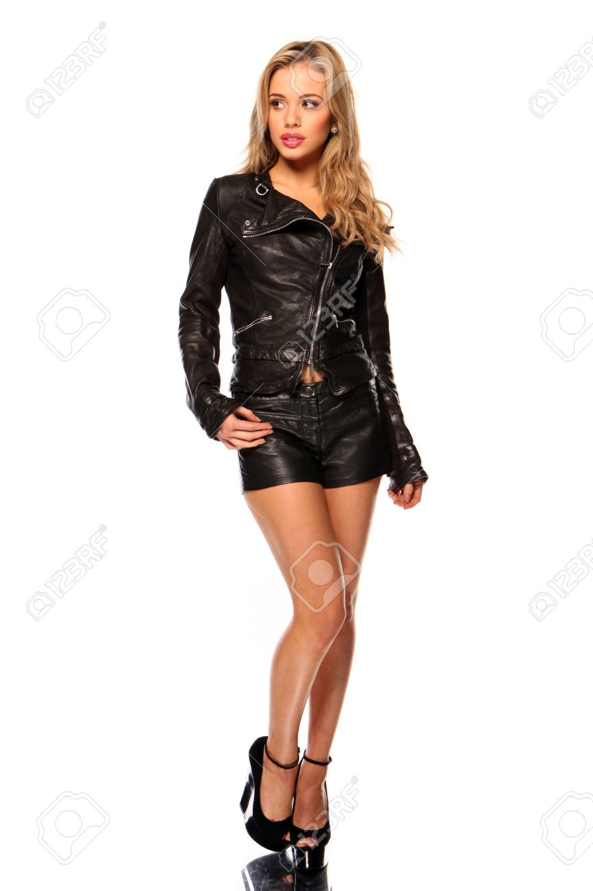 Young woman in leather and shorts looking shyly to her right - 12586034