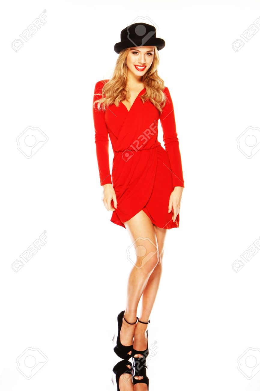 A beautiful blonde fashion model in chic red outfit showing off her long slim legs. - 12586014