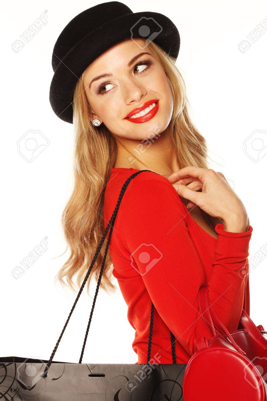 Fashionable blonde woman in chic red outfit and hat giving over-the-shoulder look. - 12586977