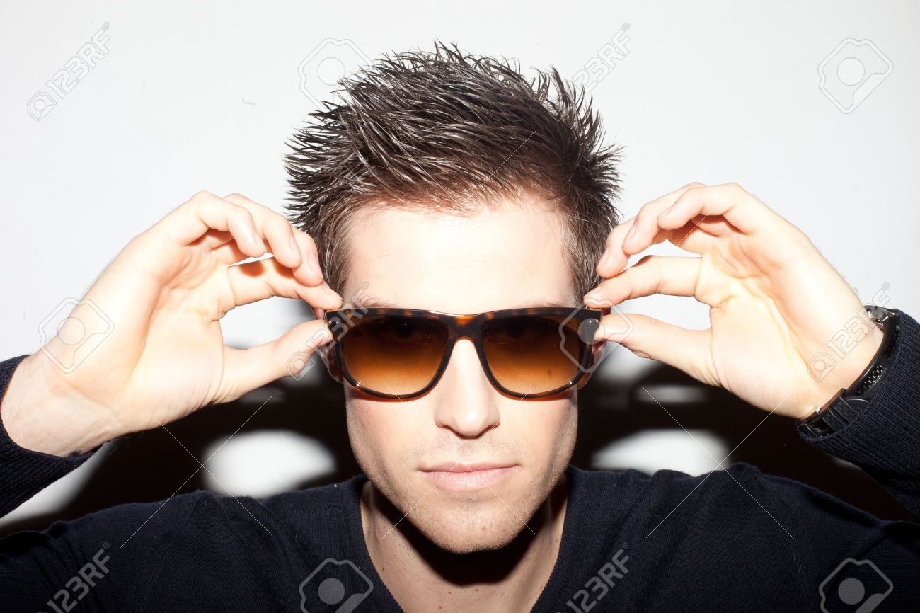Trendy young man with spiky hair with his hands raised to a pair of sunglasses. Stock Photo - 12590023