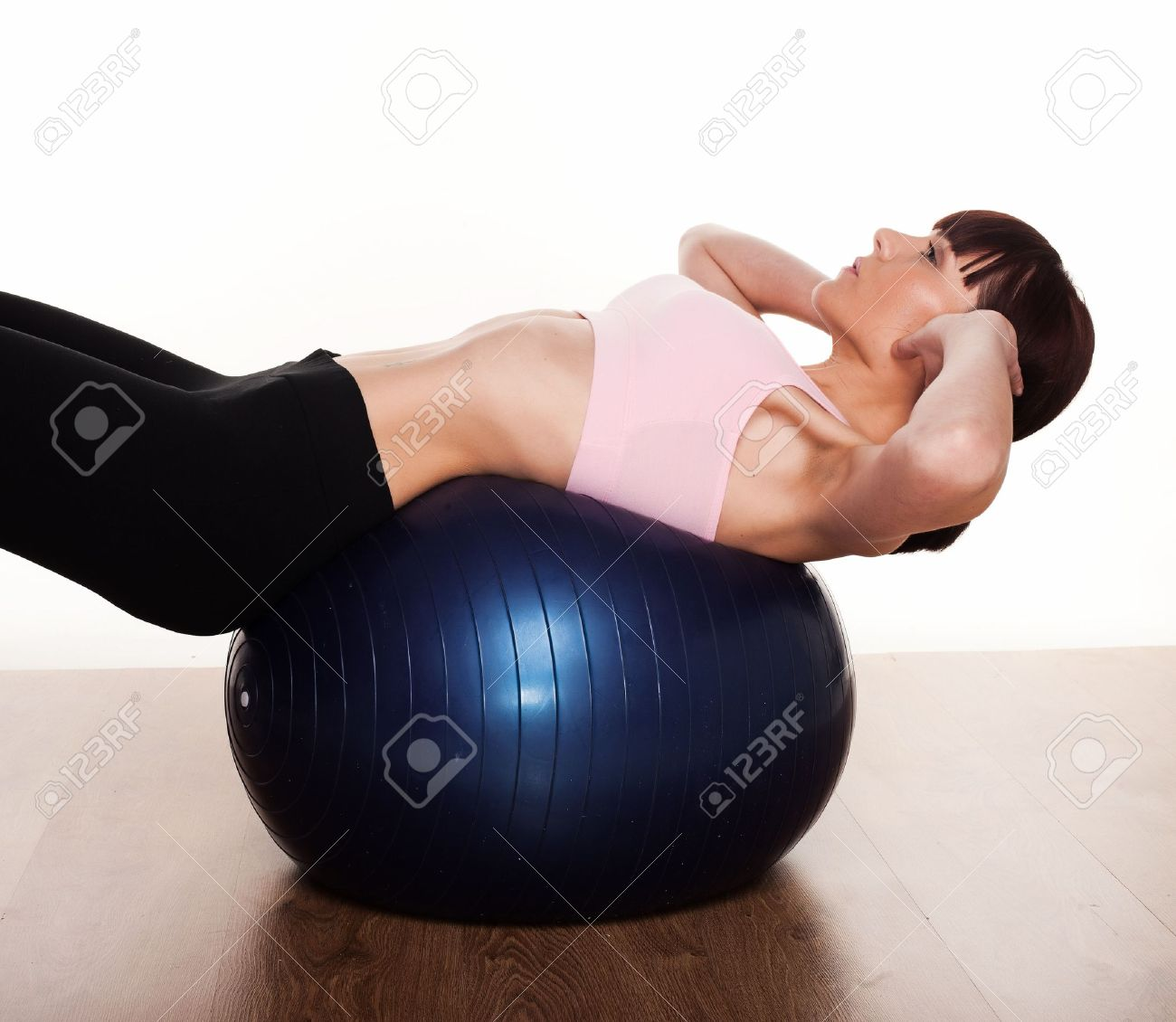 Woman leaning backwards over a pilates ball exercinig her stomach and back muscles - 12586369