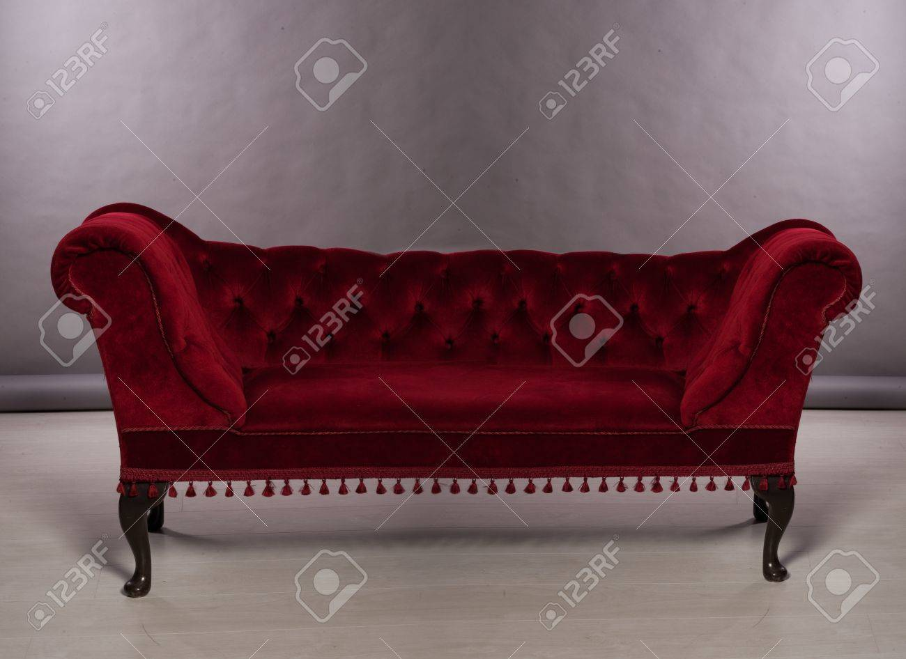 Upholstered chesterfield sofa with a button back in deep maroon..