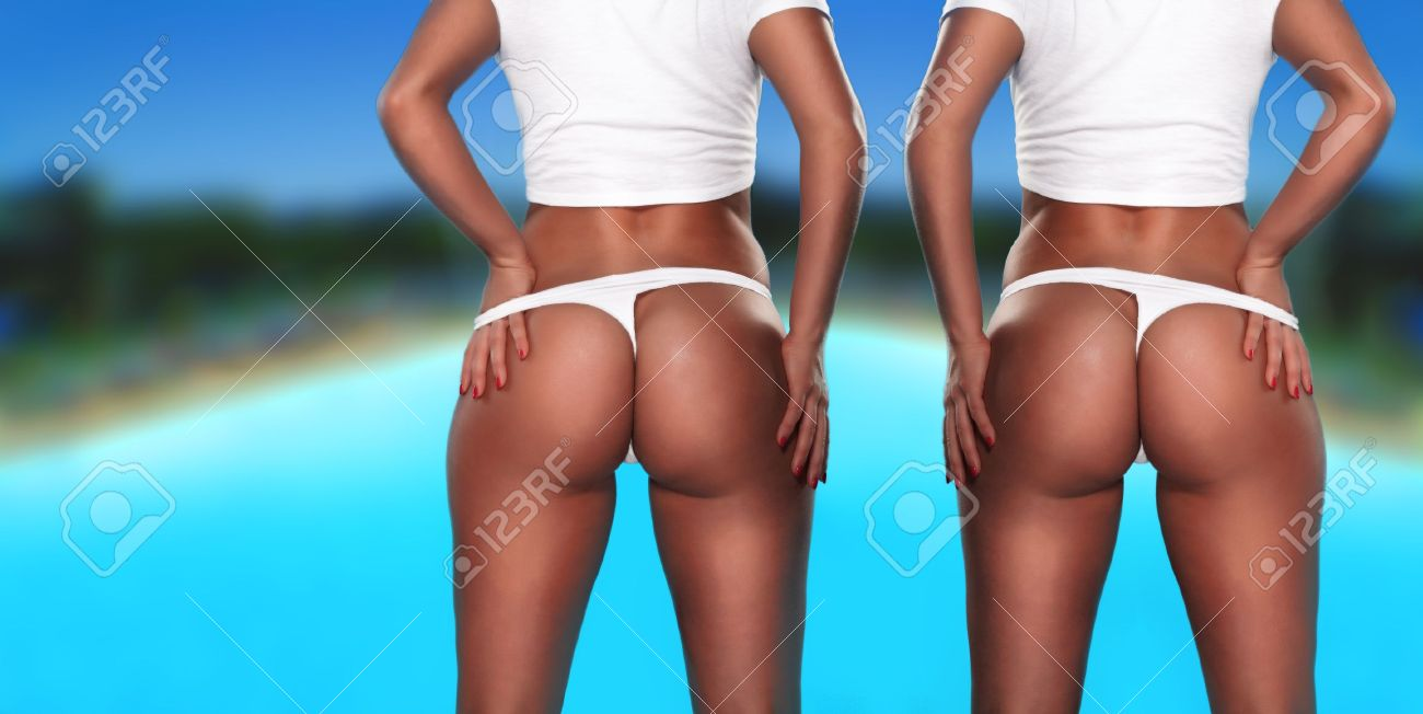 Stock Photo Twin Sexy Asses Two Women Toned Behinds In White Thong Facing Away From The Camera Shoulders Down Shot