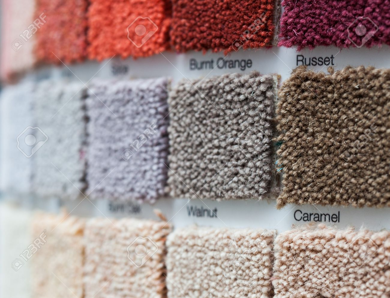 Carpet display in a retail shop with multiple square samples showing variations in colour and pile quality at an oblique angle with shallow dof Stock Photo - 21338486