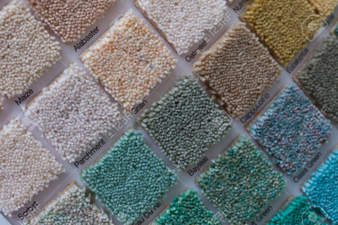 Colourful carpet display in a shop with square samples wall mounted in a variety of colours to plan your interior decor and renovation - 21338490