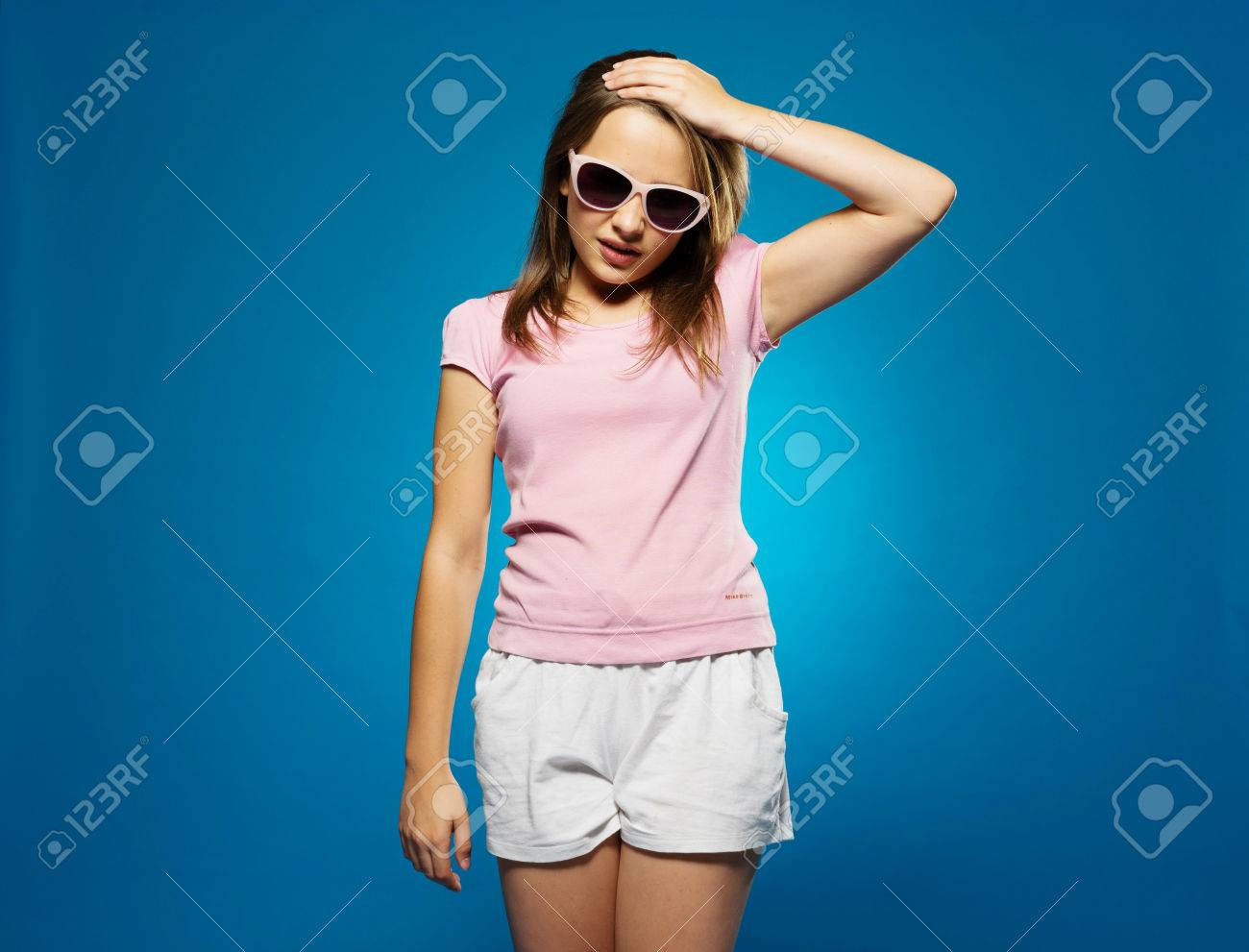21fb25e6e32 Stock Photo - Trendy young girl in summer shorts and sunglasses with a  headache clutching her forehand with her hand and grimacing in pain