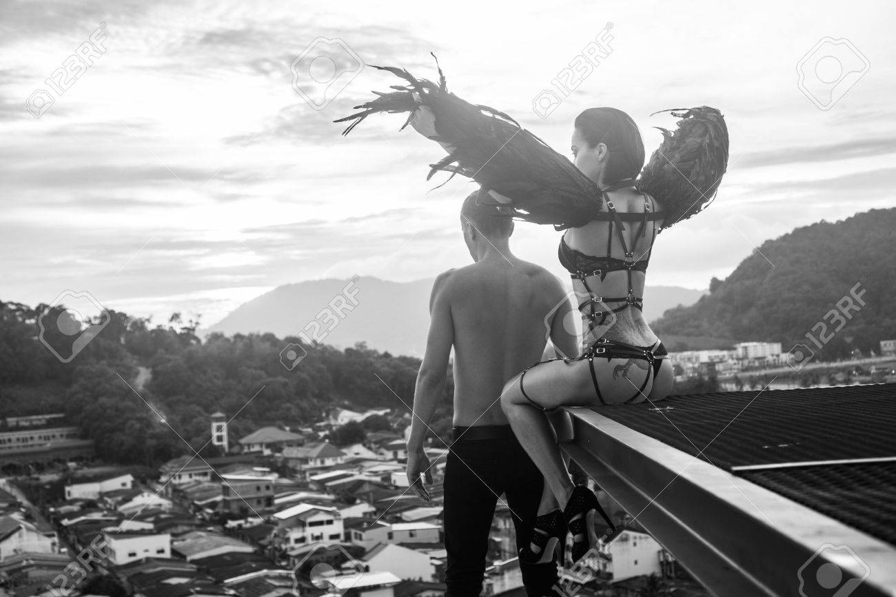 Black and white photo of romantic scene with shirtless man and sensual angel woman wearing lingerie