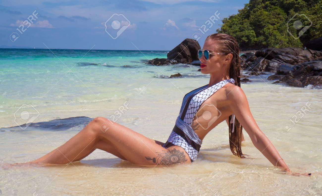a49b9cb8a9c3 Mujer morena sensual en elegante traje de baño sentado en el agua en la  playa de arena por las rocas sobre el hermoso mar laguna, cielo azul y  fondo ...