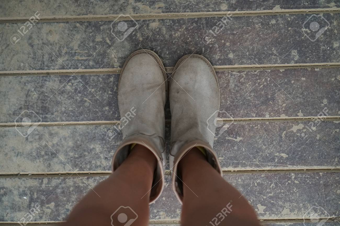 6ad52367611 Top view of woman's suede ankle boots standing on dirty wooden..