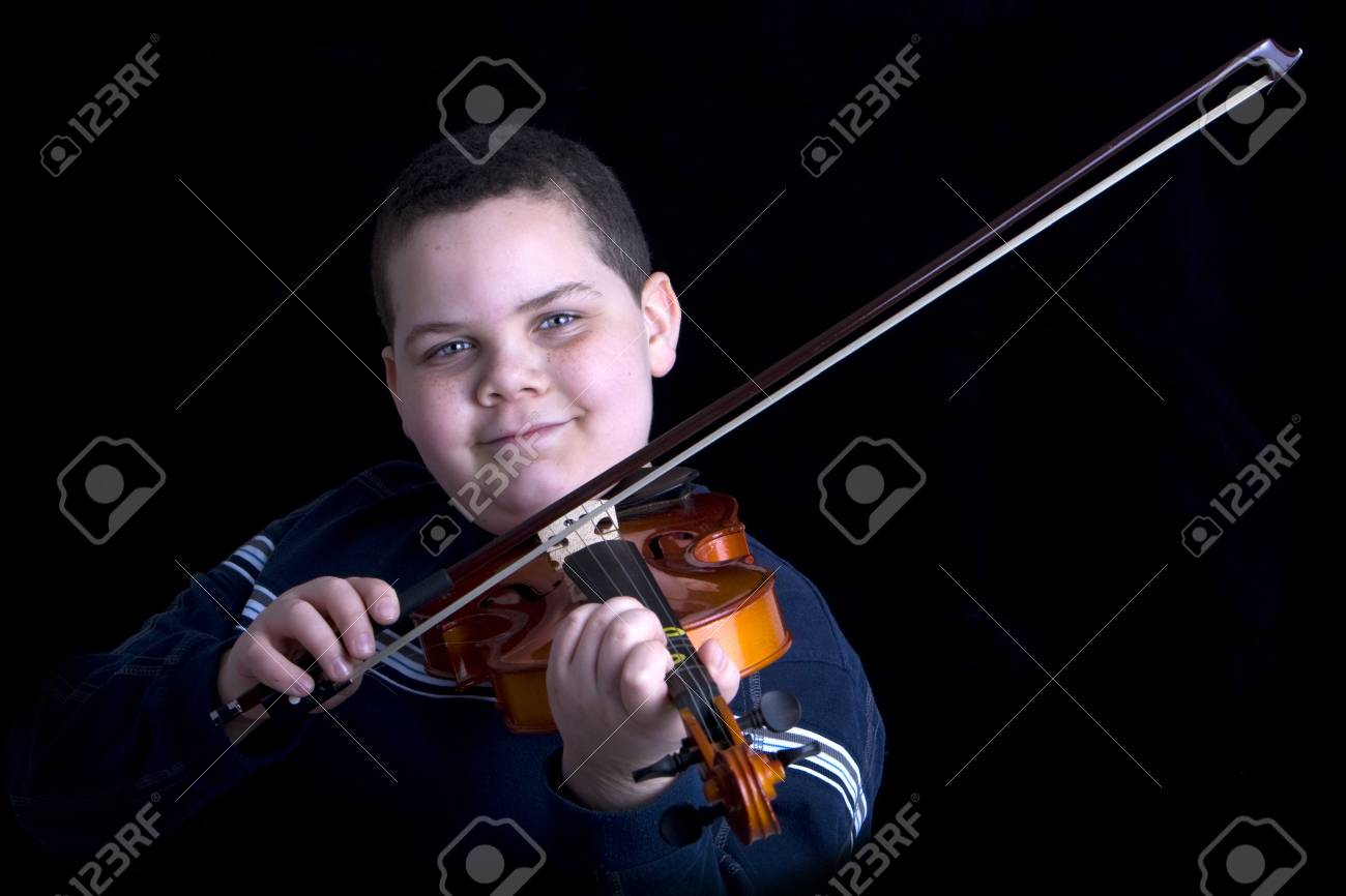 Young boy playing a violin against a black background