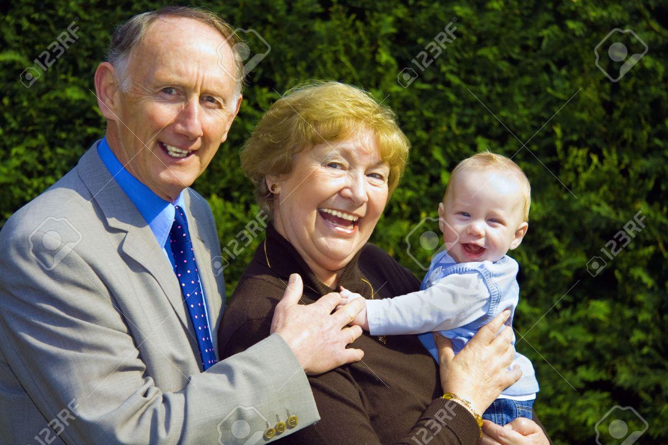 Smiling grandparents holding happy baby boy portrait Stock Photo - 3264265