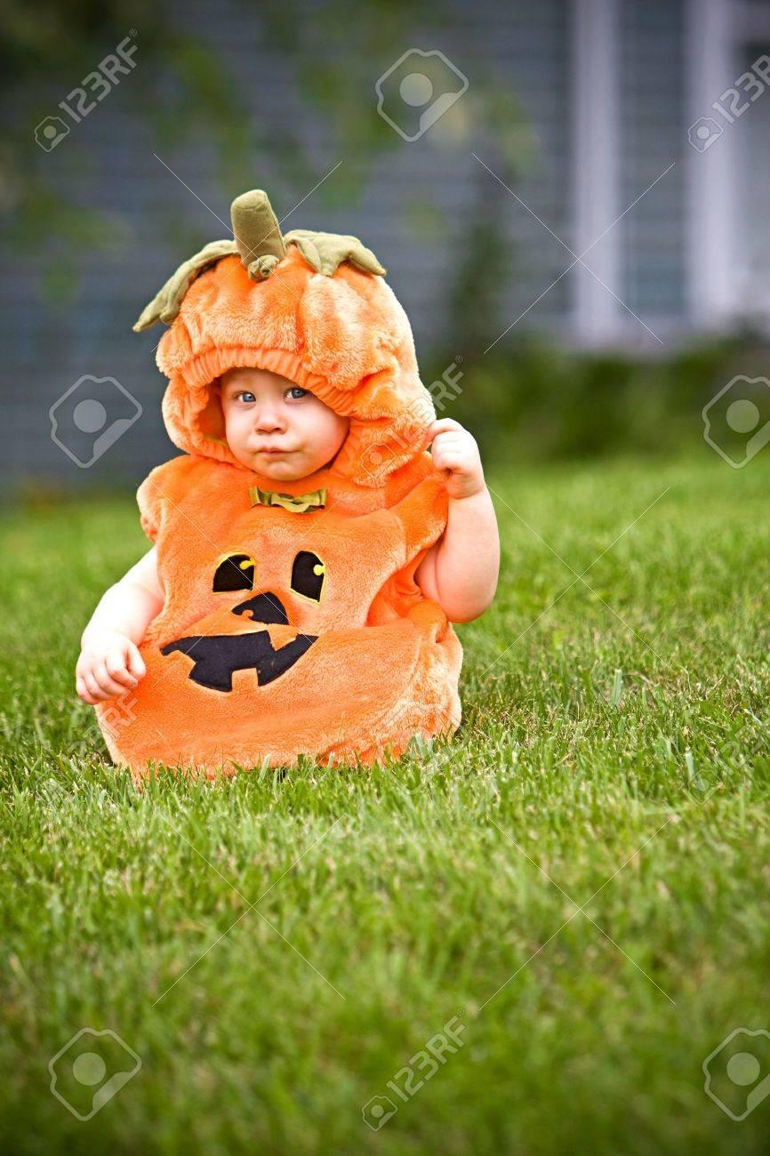 Baby in a halloween pumpkin costume sitting on grass - 3603268