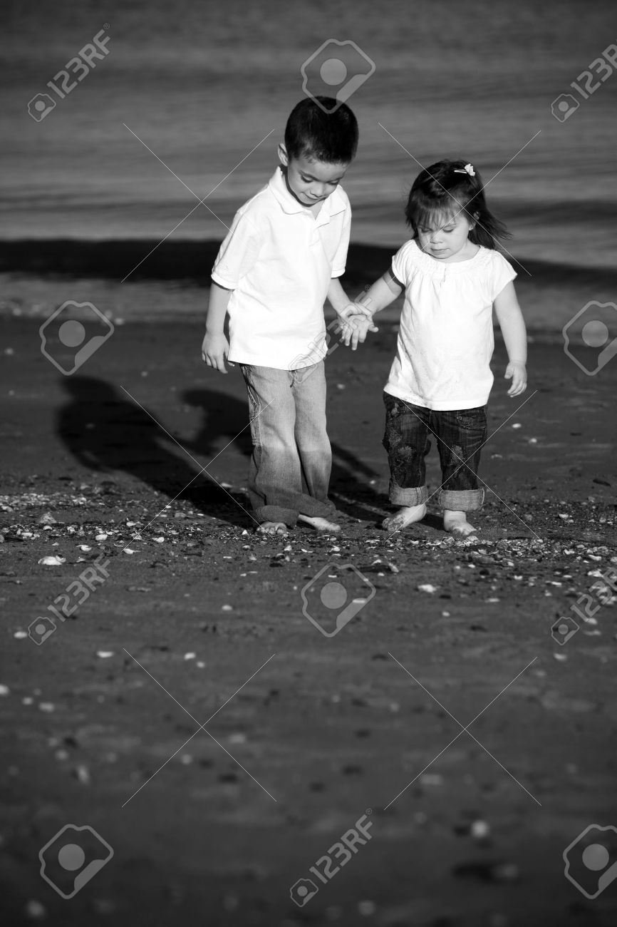 Brother and sister walking hand in hand at the beach Stock Photo - 7090762